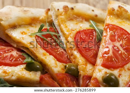 Pizza vegetarian on plate on stone black try with fresh tomatoes and olives - stock photo