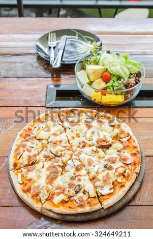 Pizza vegetarian with mushroom and pineapple on wood table in restaurant. - stock photo