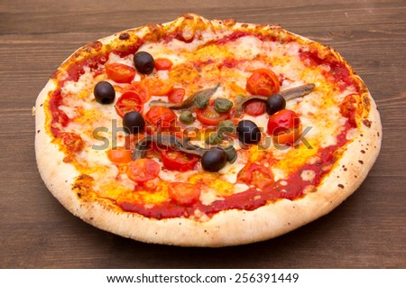 Pizza with anchovies and olives on wooden table - stock photo