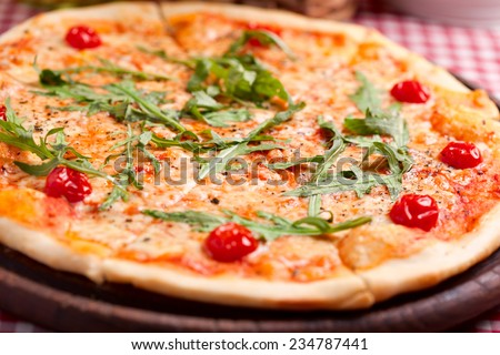 Pizza with arugula and tomatoes on wooden board - stock photo