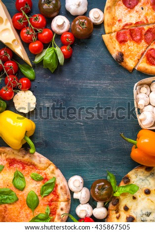 Pizza with assorted toppings and ingredients background. Space for text. Pizza, flour, cheese, tomatoes, basil, pepperoni, mushrooms and rolling pin over wooden background. Top view. Food frame
