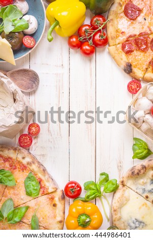 Pizza with assorted toppings and ingredients background. Space for text. Pizza, flour, cheese, tomatoes, basil, pepperoni, mushrooms and rolling pin over white wooden background. Top view. Food frame