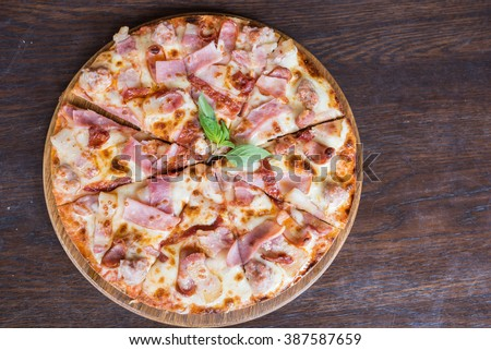 pizza with bacon ham and sausage on wooden table, Top view - stock photo
