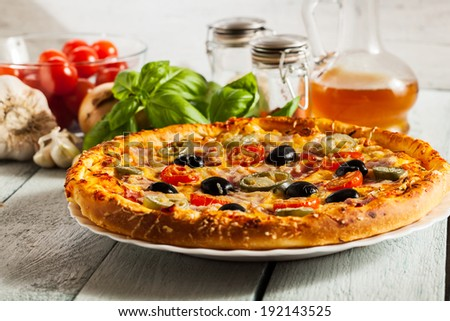 Pizza with bacon, olives and jalapeno pepper on a plate