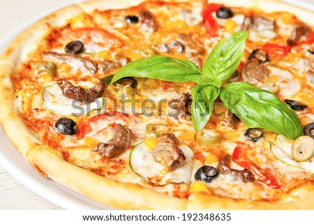 Pizza with bacon, olives, tomatoes, cucumber, cheese and basil - stock photo