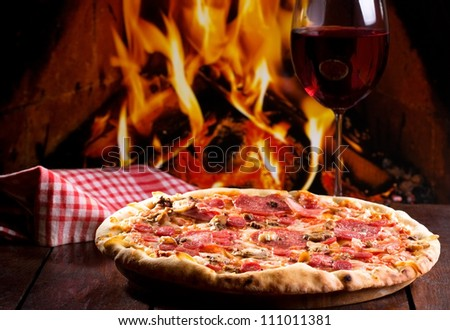 pizza with bacon, salami and glass of wine - stock photo