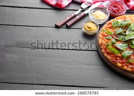 Pizza with basil on cutting board on wooden background - stock photo