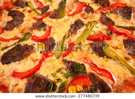 Pizza with beef, sweet pepper, cucumber, sweet corn, cheese and greens close-up, selective focus, macro. Italian cuisine. - stock photo