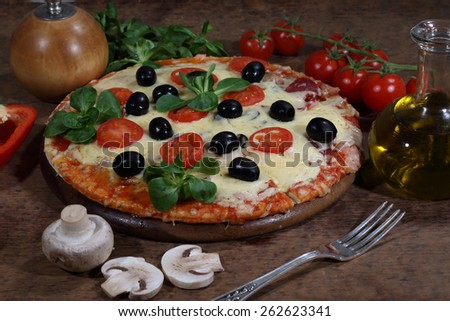 Pizza with cheese, a salami, mushrooms, tomatoes, olives and Rucola - stock photo