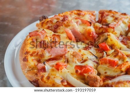 Pizza with chicken, pork tomato and pineapple.