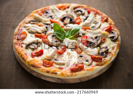 Pizza with chicken, tomato and mushrooms - stock photo