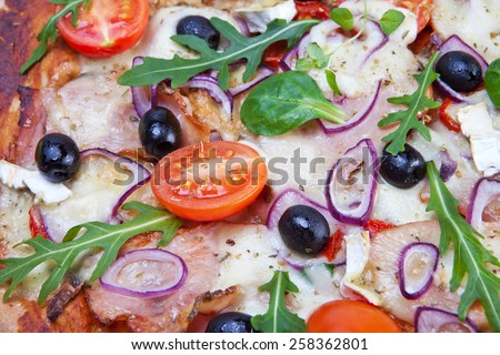 Pizza with dry cured ham and salad - stock photo