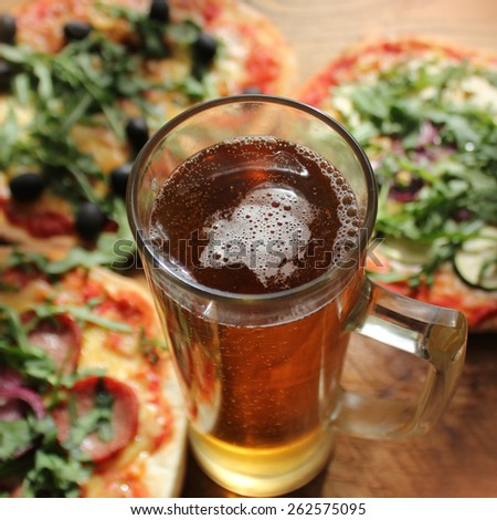 Pizza with glass of beer served on table - stock photo