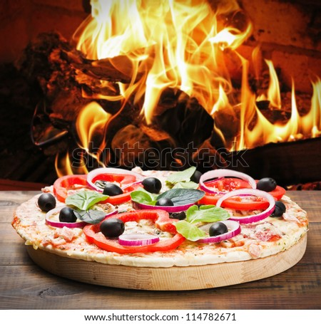 pizza with ham and cheese cooked on the fire in the stove - stock photo