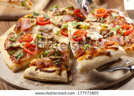 Pizza with ham and mushrooms on plate - stock photo