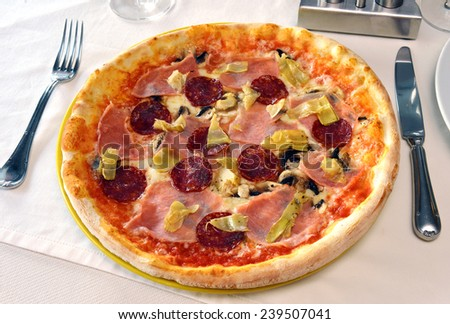 pizza with ham and salami on a plate - stock photo