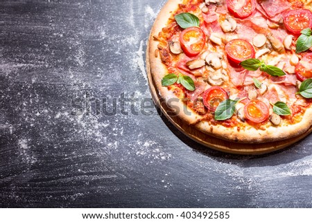 pizza with ham and vegetables on dark background - stock photo