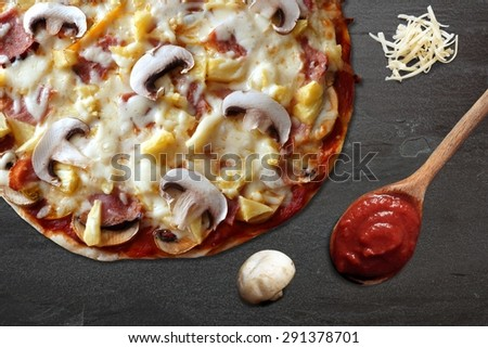 Pizza with ham, mushroom and pineapple against a slate stone background with shredded mozzarella cheese and spoon of tomato sauce - stock photo