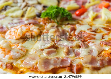 Pizza with ham, mushroom, bacon and salami in restaurant.
