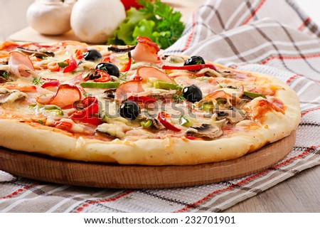 Pizza with ham, mushrooms and olives - stock photo