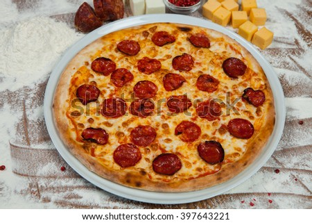 Pizza with ham, pepper and olives. Delicious fresh pizza served on wooden table. Pizza with tomato, salami, olives and cheese. - stock photo