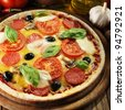 Pizza with ham, pepper and olives on wooden board - stock photo