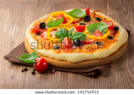Pizza with ham, tomato and olives and vegetables on wooden table