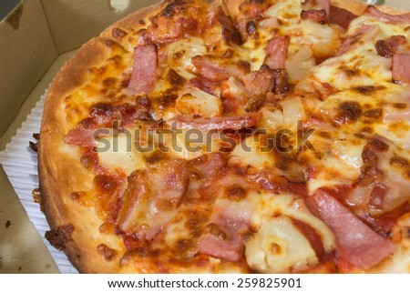 Pizza with Hawaiian pineapple and ham, topped with cheese - stock photo