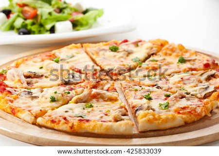 Pizza with Mozzarella, Bacon and Mushrooms. Served with Greek Salad - stock photo