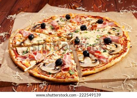 Pizza with Mozzarella, Bacon, Mushrooms and Olives - stock photo