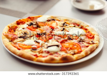 Pizza with Mozzarella Cheese, Fresh Tomato and Mushrooms. Served at Restaurant Table - stock photo