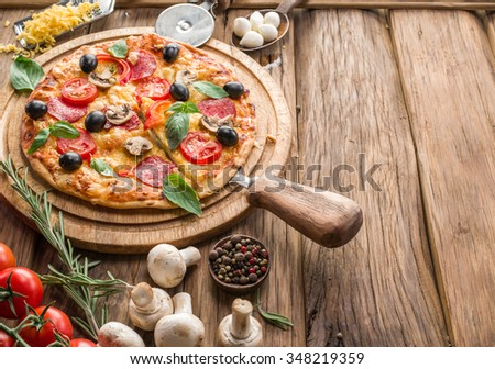 Pizza with mushrooms, salami and tomatoes. Top view. - stock photo