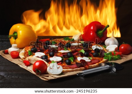 Pizza with oven fire on background - stock photo
