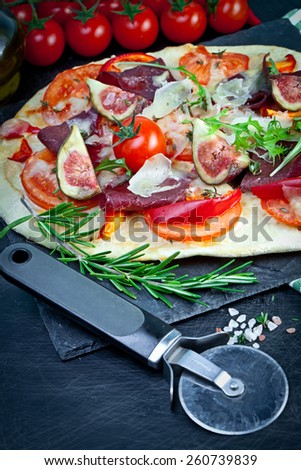 Pizza with prosciutto and figs - stock photo