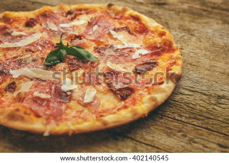 pizza with prosciutto ham, parmesan cheese and dried tomatoes  served with basil leaves on the top