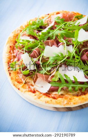 Pizza with prosciutto (parma ham), arugula (salad rocket) and parmesan on blue wooden background close up. Italian cuisine. - stock photo