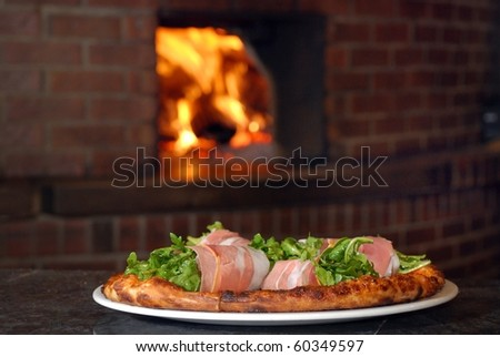 Pizza with roll of italian ham fresh out of a wood burning oven