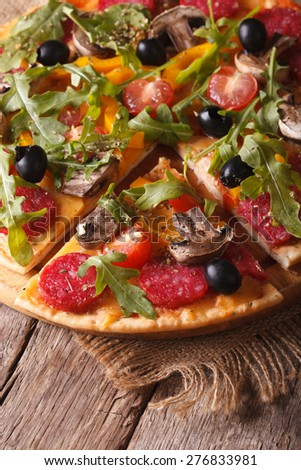 Pizza with rucola, salami and olives close-up on the table. vertical top view  - stock photo