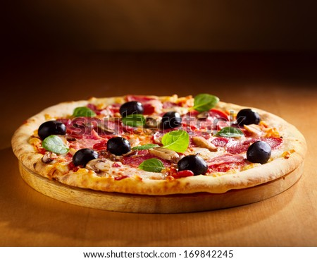 pizza with salami and bacon on wooden table - stock photo
