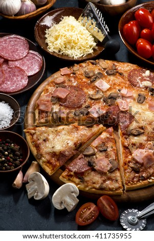 pizza with salami and ingredients on a black background, vertical, top view - stock photo