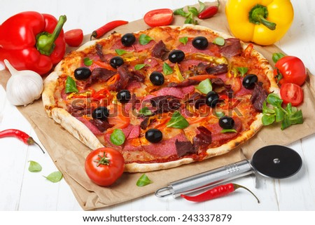 Pizza with salami, ham and black olives on wooden table - stock photo