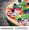 pizza with salami, olives and cheese cut into chunks - stock photo