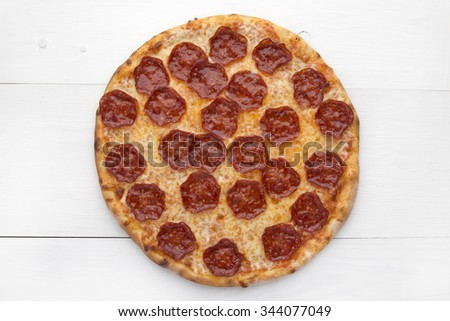 Pizza with salami on white wooden background