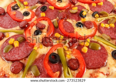 Pizza with salami, sausage, frankfurters, red pepper, cucumber, corn, green and black olives close-up, selective focus, macro - stock photo