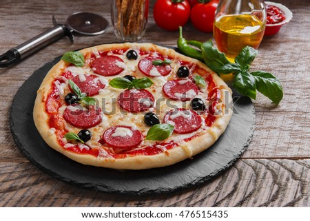 pizza with salami tomato and cheese on a wooden surface