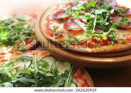 Pizza with sausage, cheese, ruccola - stock photo