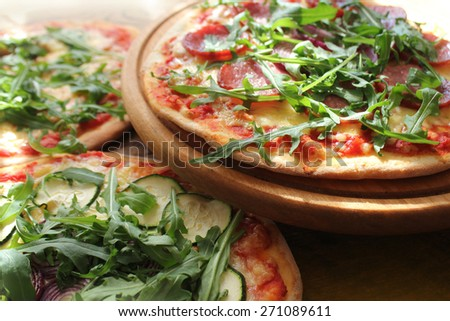 Pizza with sausage, zucchini, olives, cheese, rucola  - stock photo