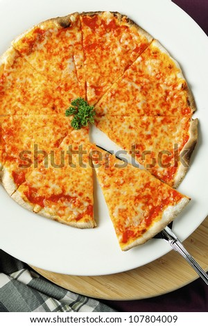 Pizza with the cut off slice - stock photo