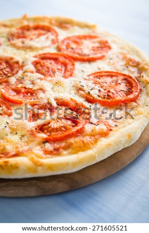 Pizza with tomato, cheese and dry basil on blue wooden background close up. Italian cuisine. - stock photo