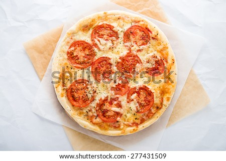 Pizza with tomato, cheese and dry basil on white background top view. Italian cuisine. - stock photo